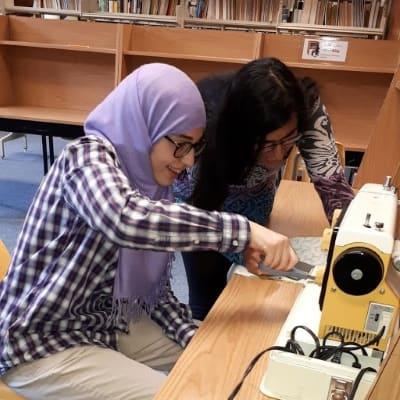 Sarah Nassar and Nisha Gill working on feast bundles